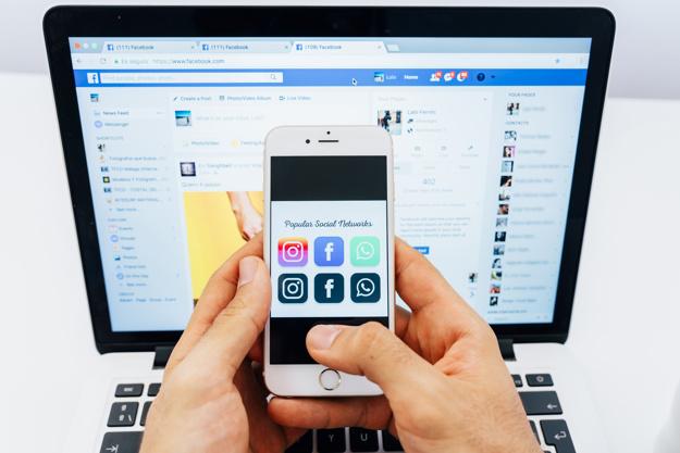 Ordenador portátil con Facebook en la pantalla y móvil con las redes sociales