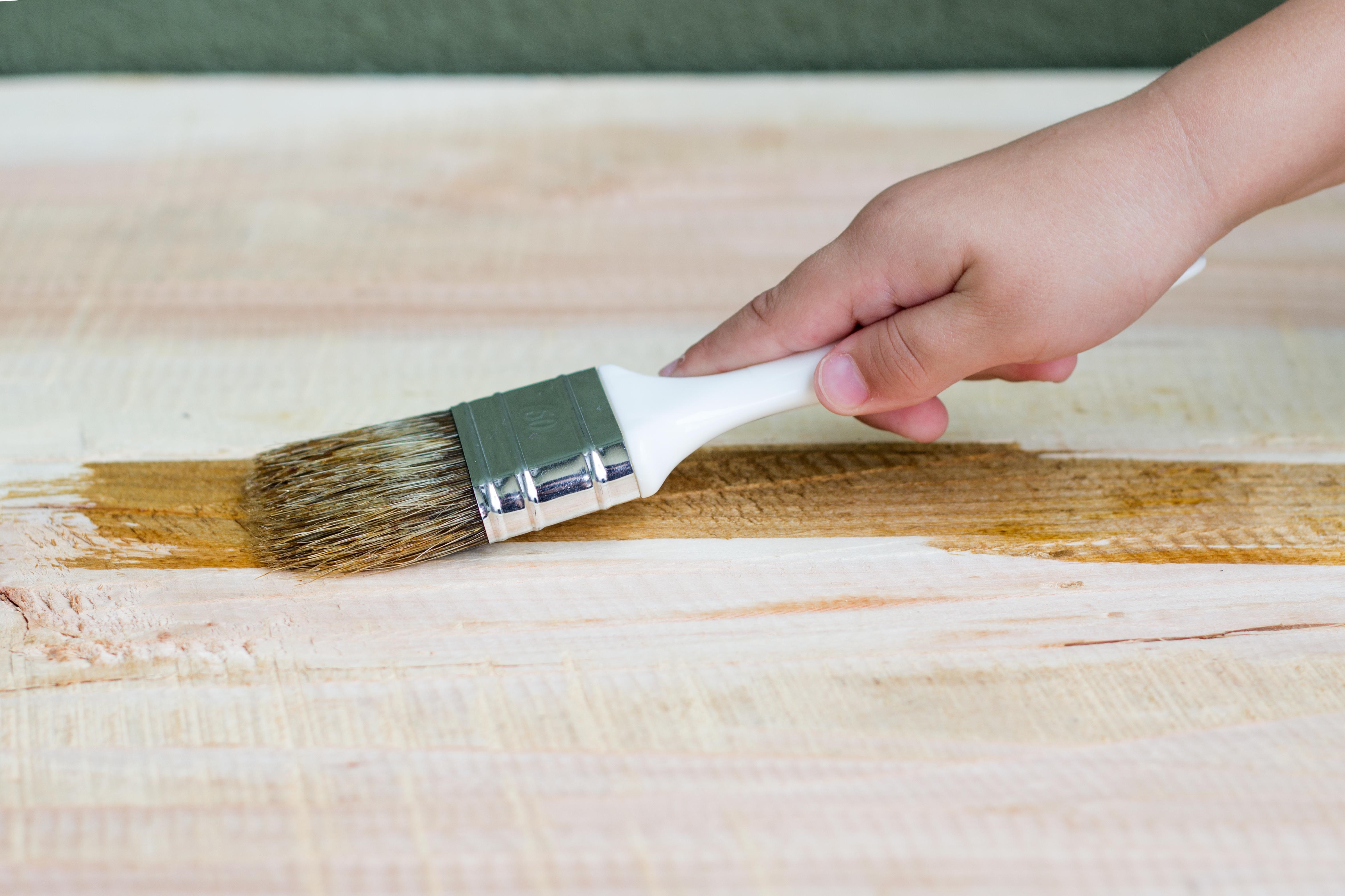 Persona barnizando madera
